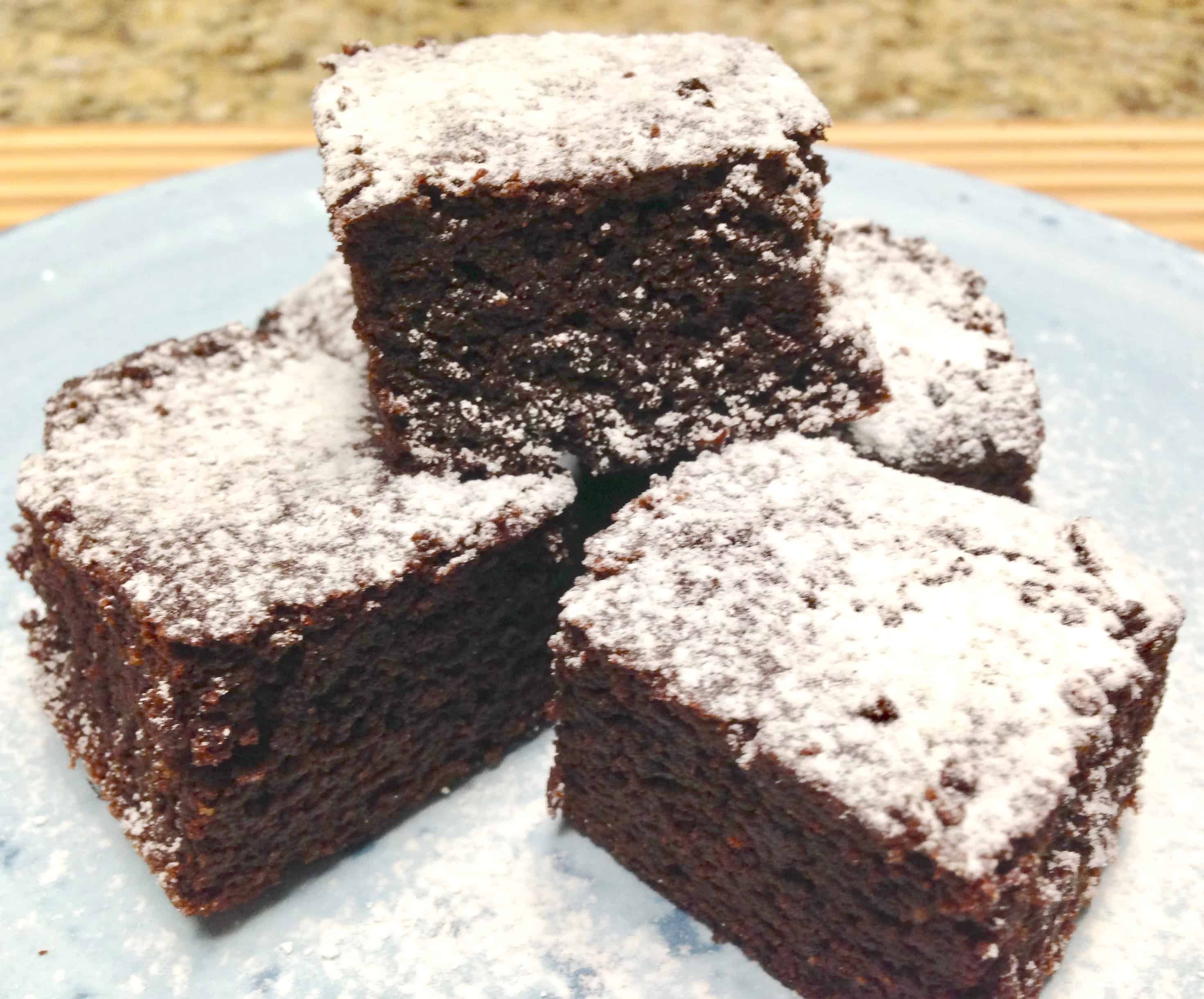 blue plate with avocado chocolate brownies on top with powdered sugar