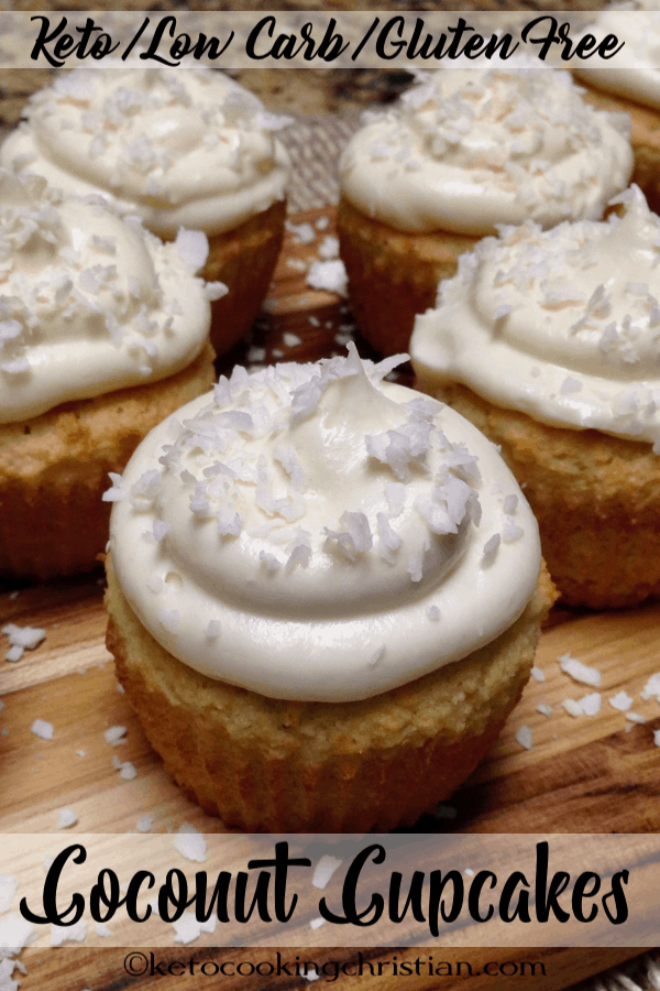 coconut cupcakes with coconut frosting on cutting board with shredded coconut on top