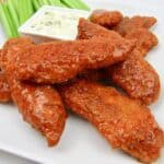 closeup of buffalo tenders on white plate with celery
