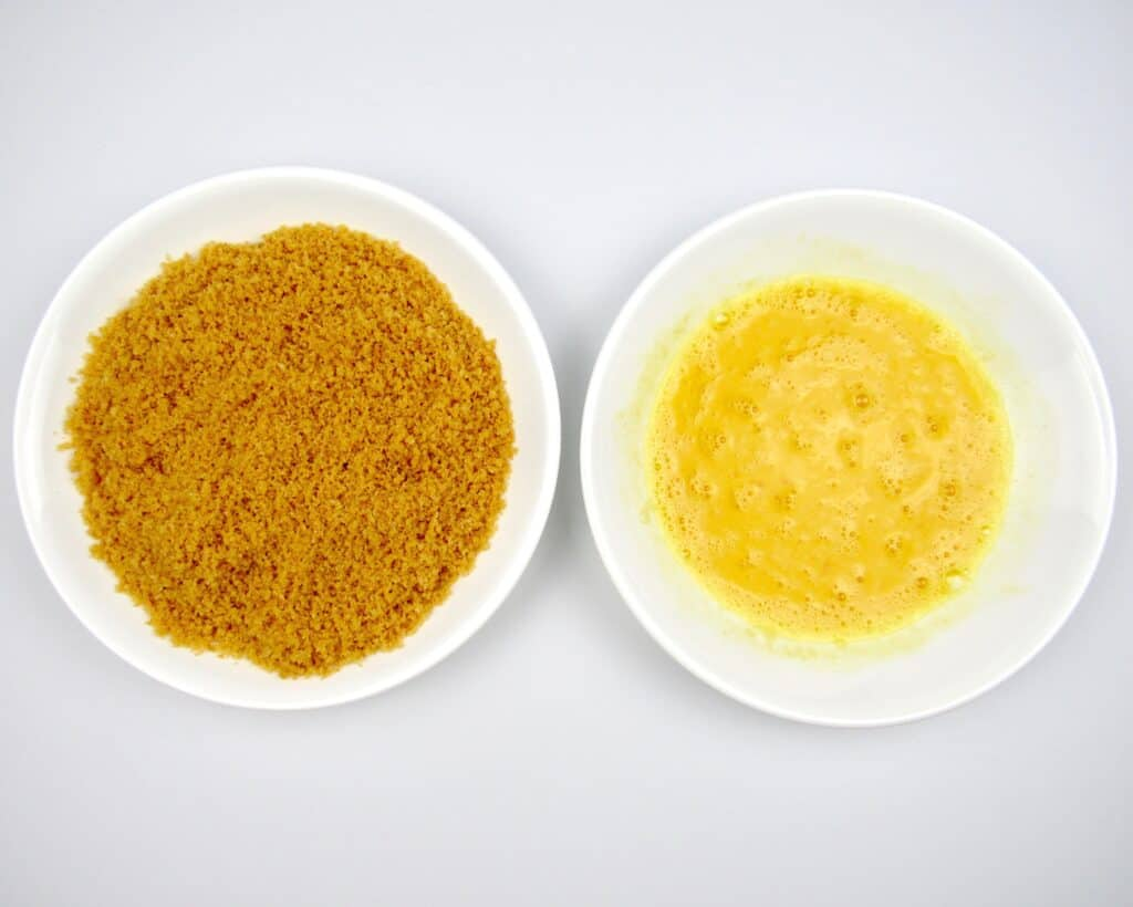 bread crumbs in white bowl with beaten eggs in another