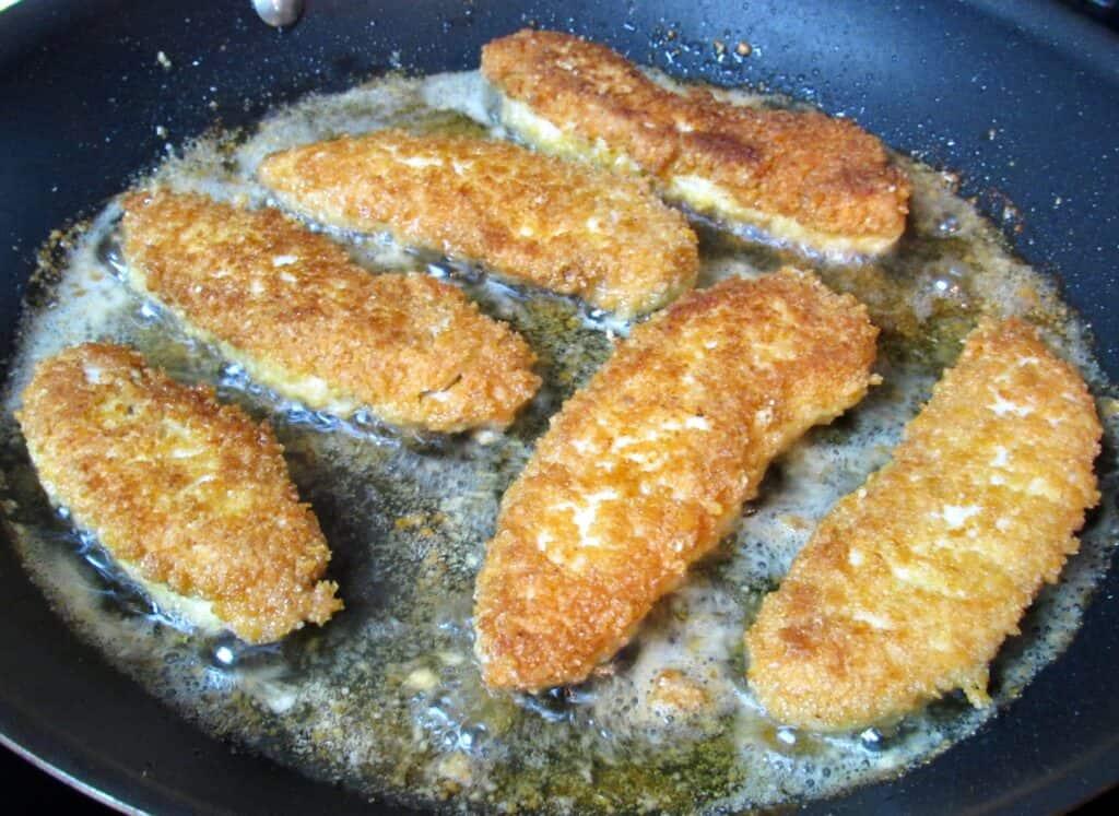 chicken tenders being fried in skillet