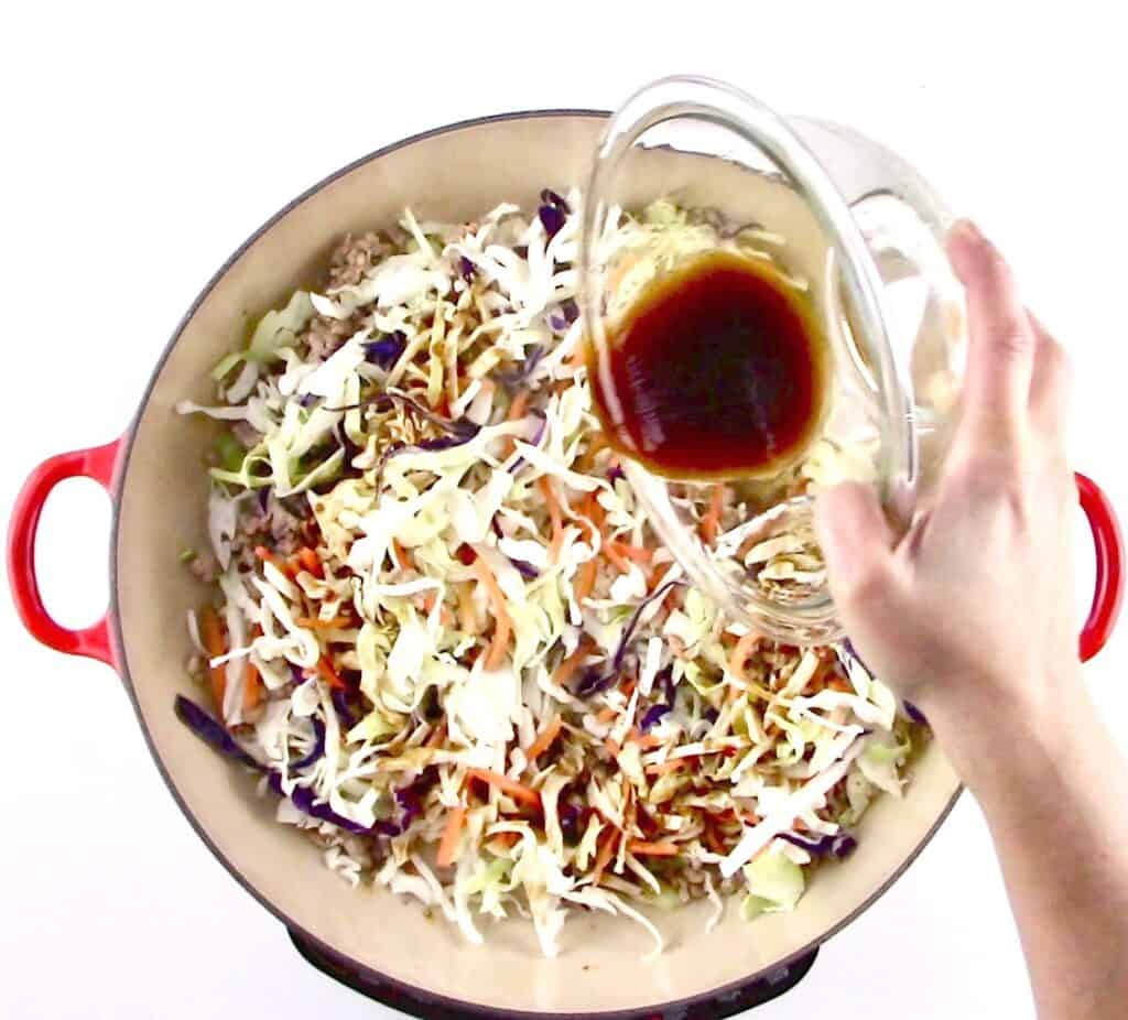 ground pork and slaw mix in skillet with sauce being poured over it