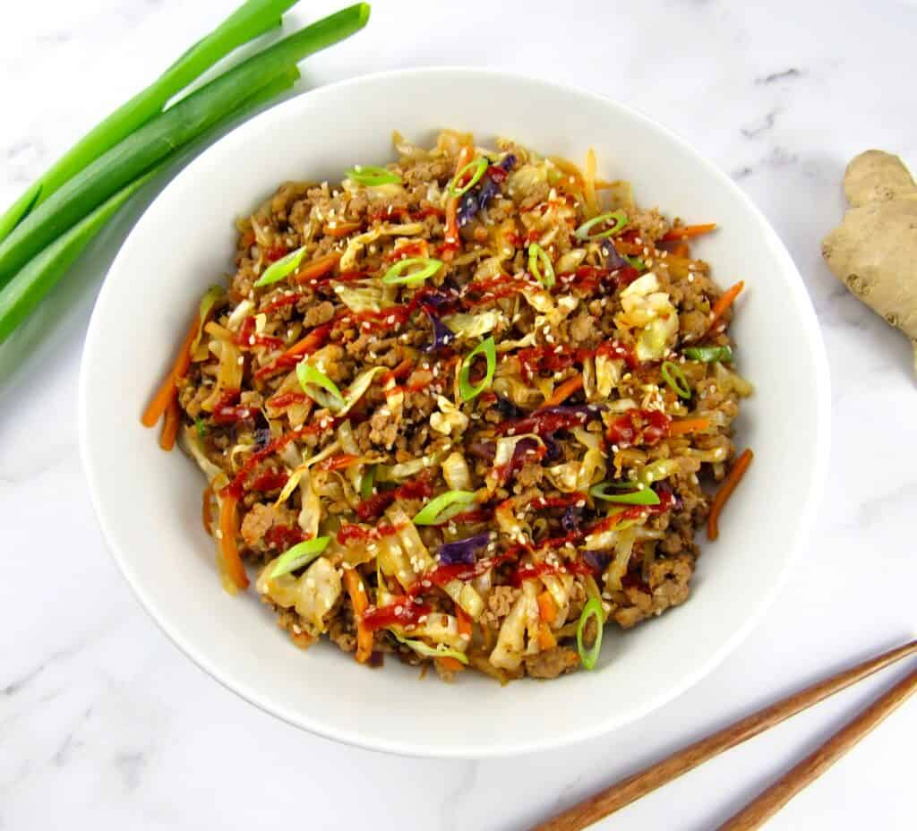 egg roll in a bowl with scallions and ginger on side