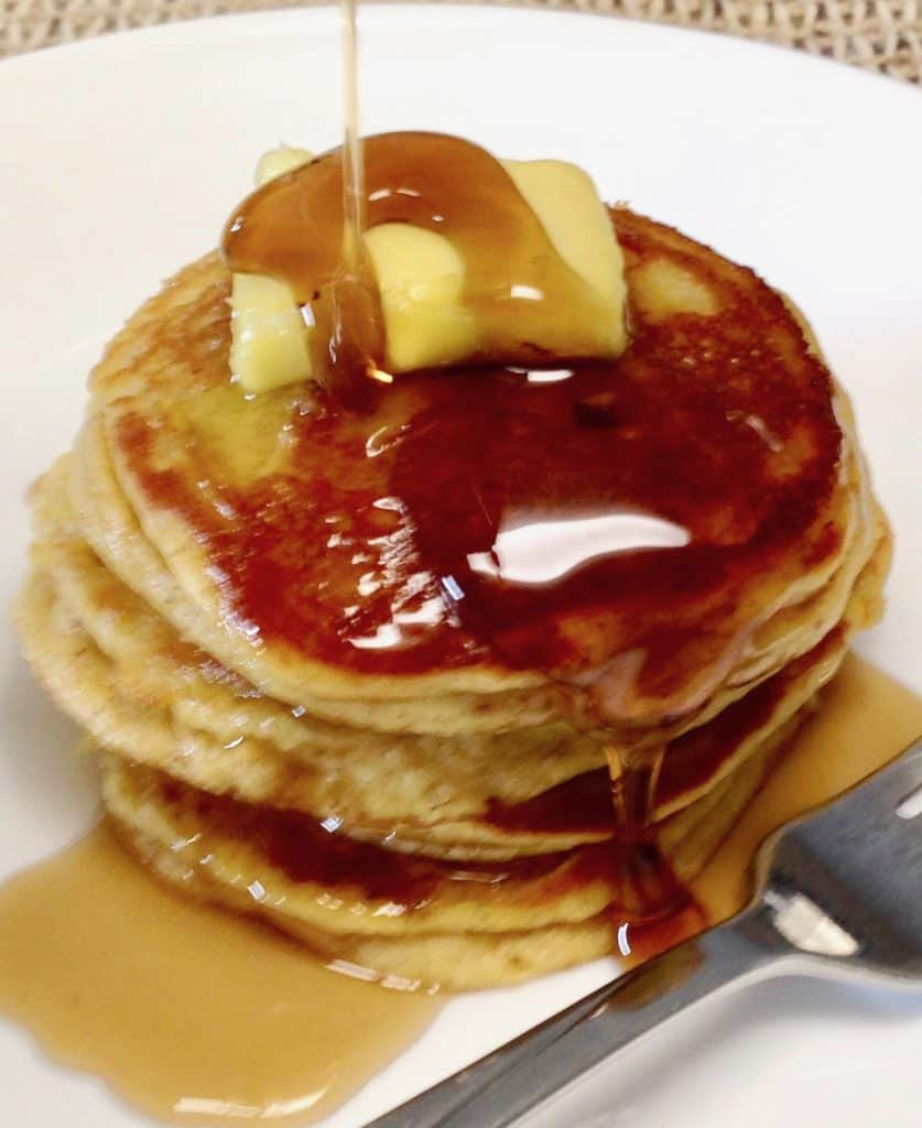 pumpkin pancakes on a plate with butter and syrup
