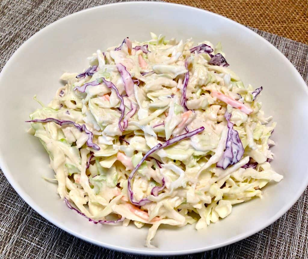 bowl of cole slaw with creamy sauce in white bowl