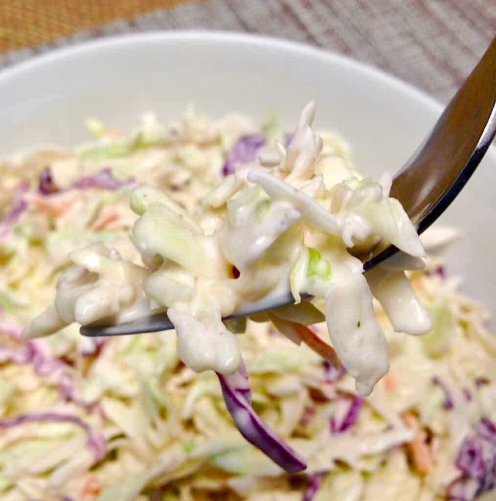 closeup of cole slaw with fork holding up a bite
