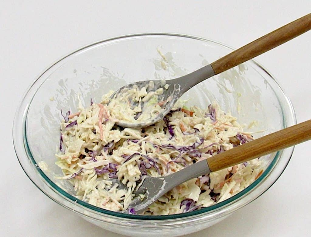 Keto Coleslaw in glass bowl mixed with utensils