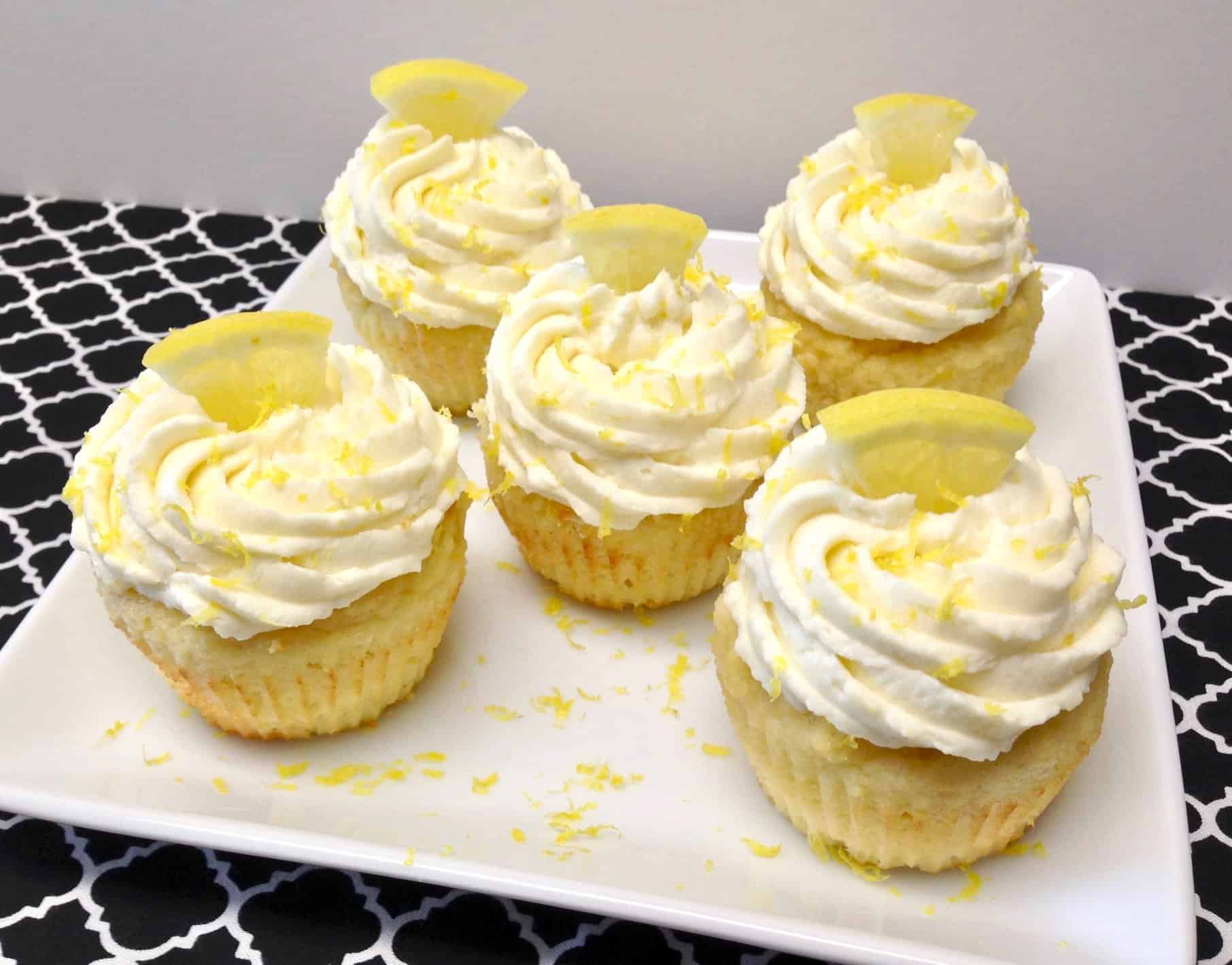5 frosted lemon cupcakes on white plate