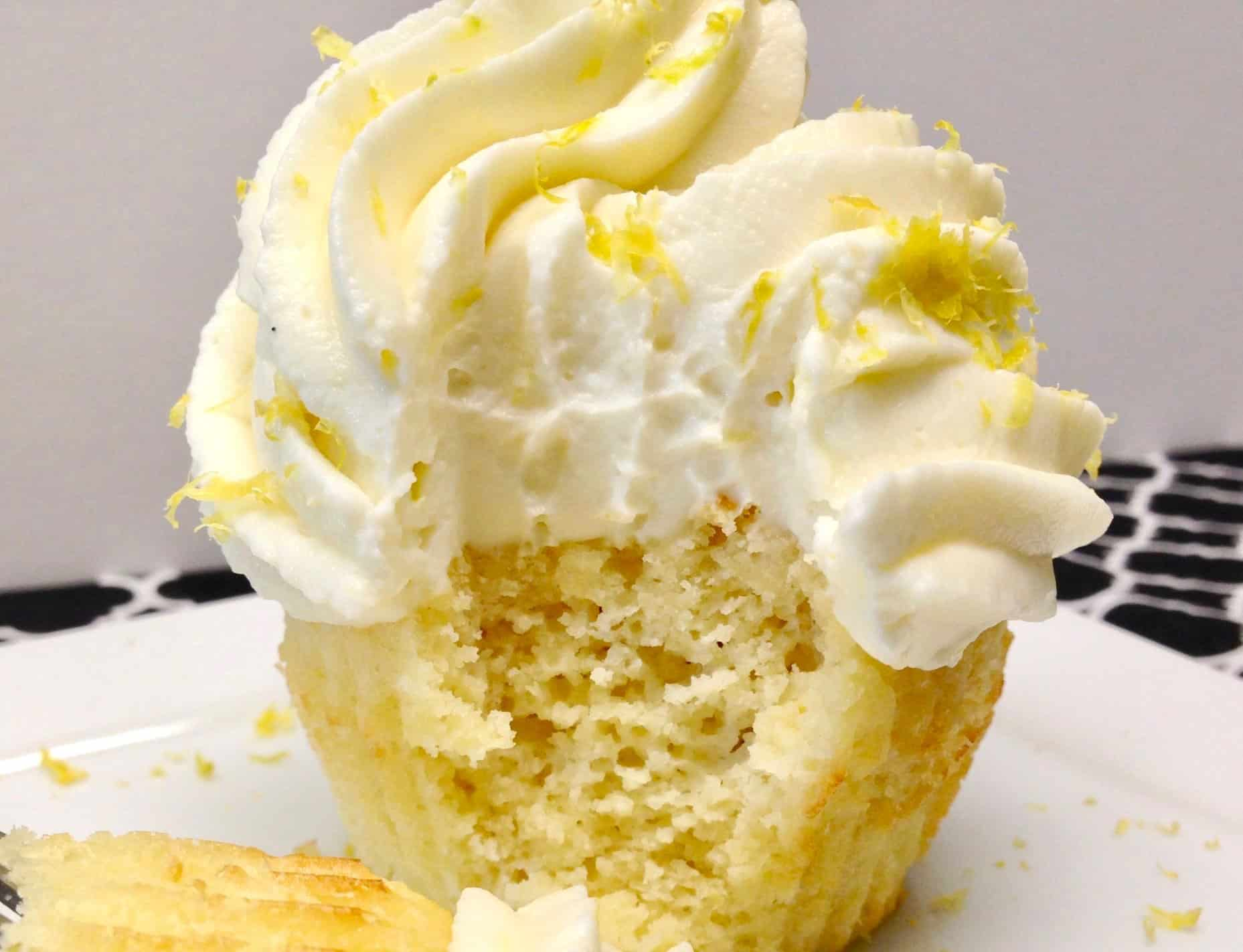 closeup of lemon frosted cupcake with bite taken out