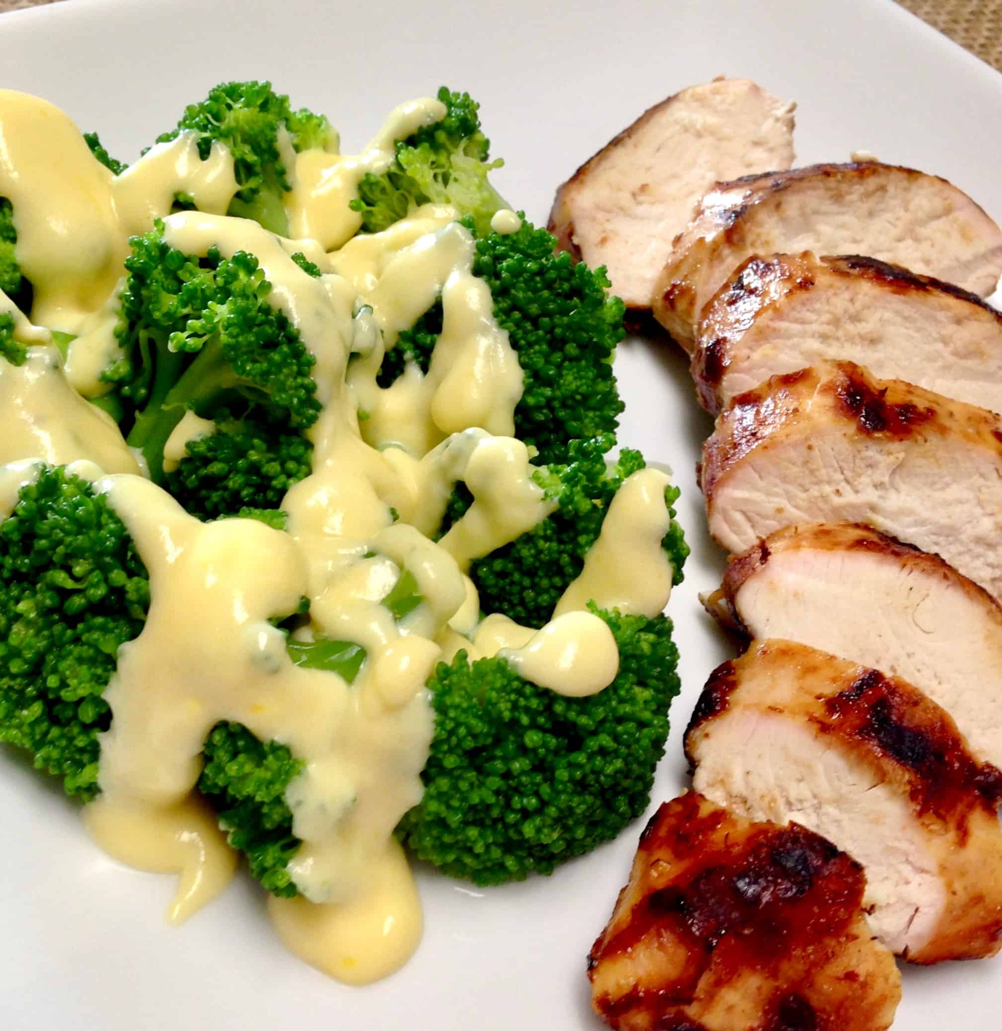broccoli with cheese sauce next to sliced grilled chicken on white plate