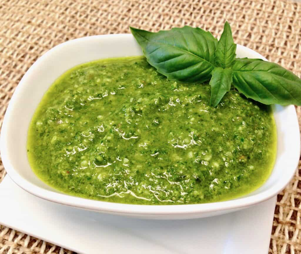 pesto sauce in white bowl with basil leaf