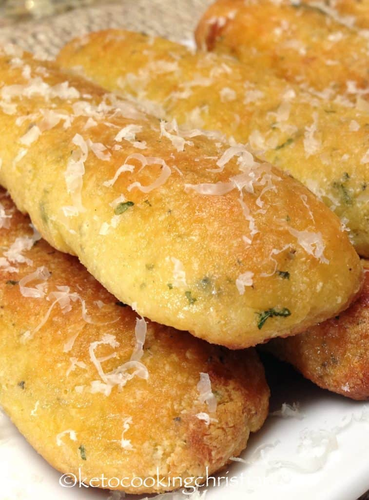 breadsticks on a plate with grated parmesan over the top