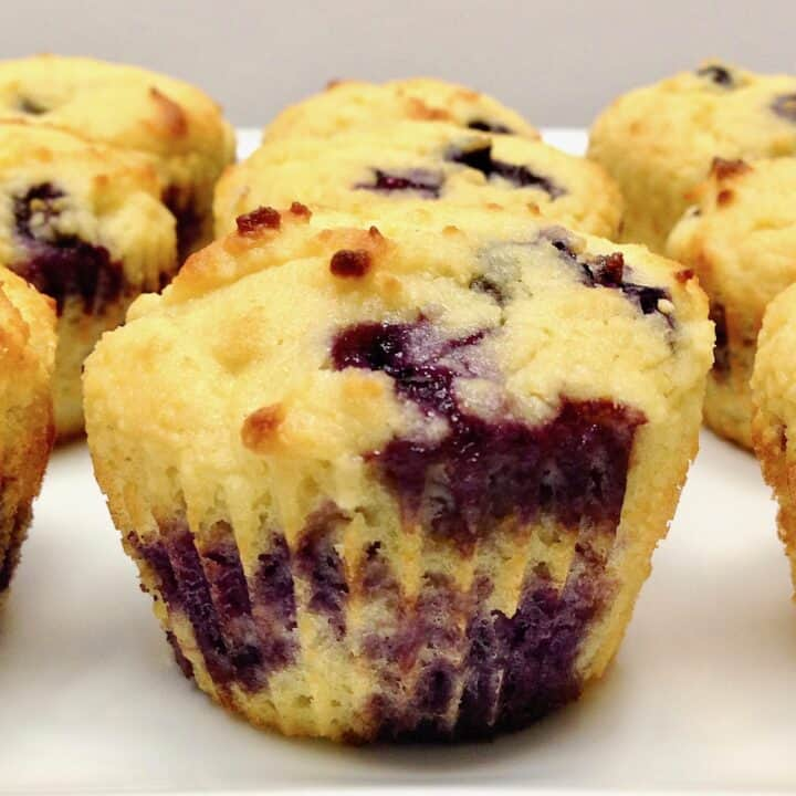closeup of a blueberry muffin on white plate