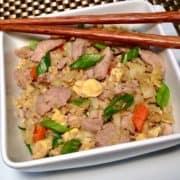 Keto Pork Fried Cauliflower Rice in white bowl with chopsticks
