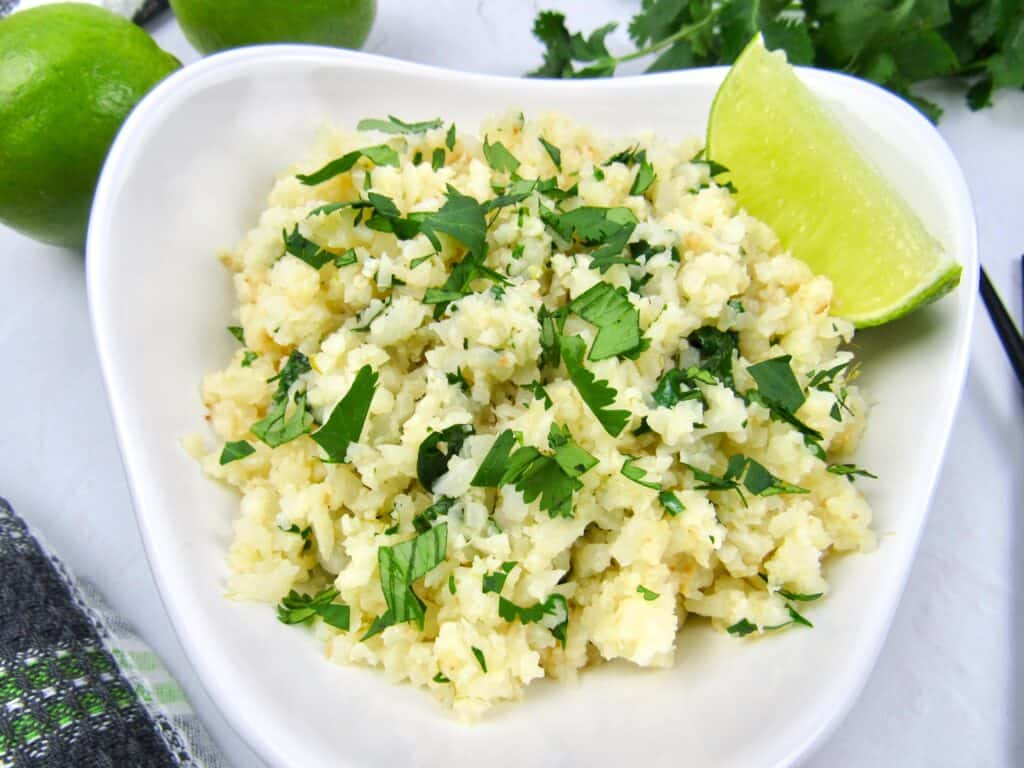 closeup of Lime cilantro cauliflower rice in white bowl with lime wedge