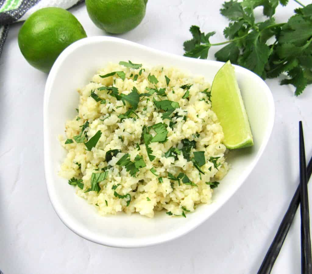Lime cilantro cauliflower rice in white bowl with lime wedge