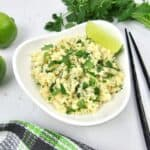 white bowl with lime cilantro cauliflower rice with limes and cilantro garnish