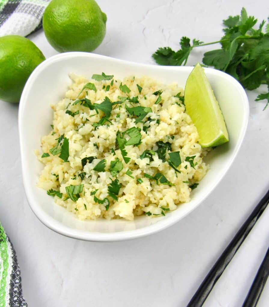 Lime cilantro cauliflower rice in white bowl with lime wedge and limes in background