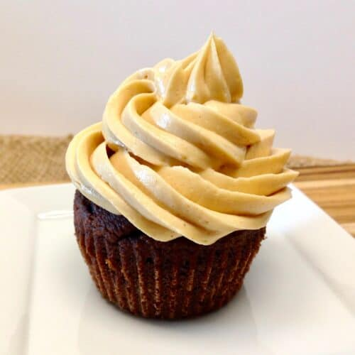 closeup of chocolate cupcake with peanut butter frosting on white plate