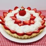 strawberry cream tart decorated with whip cream and fresh strawberries on top