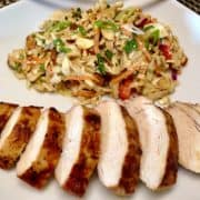 asian grilled chicken sliced on white plate with ginger slaw
