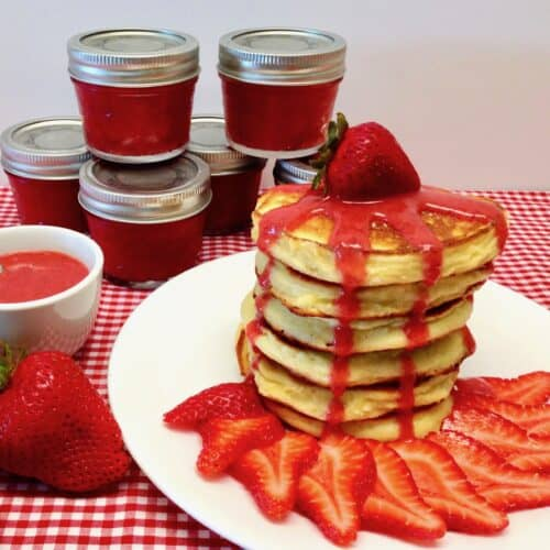 stack of pancakes with strawberry sauce and strawberry on top