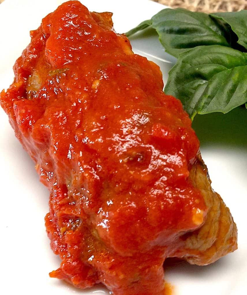 braciole with marinara sauce on top with basil garnish