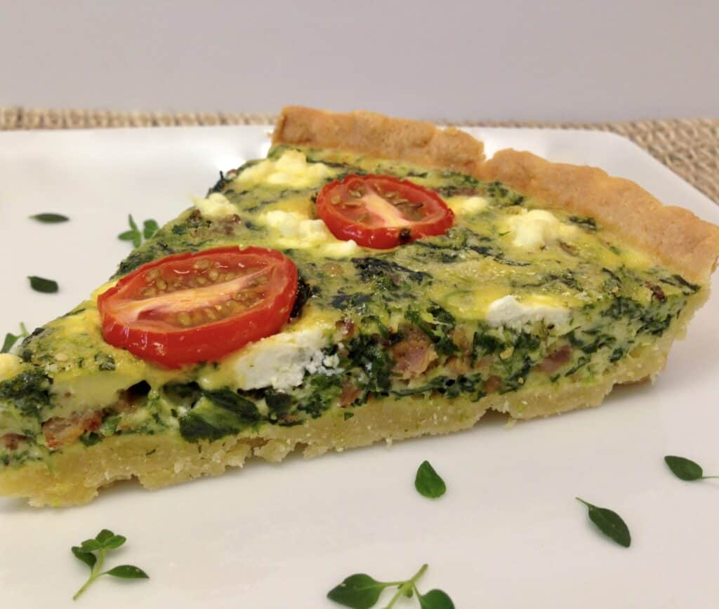 closeup slice of spinach quiche on plate