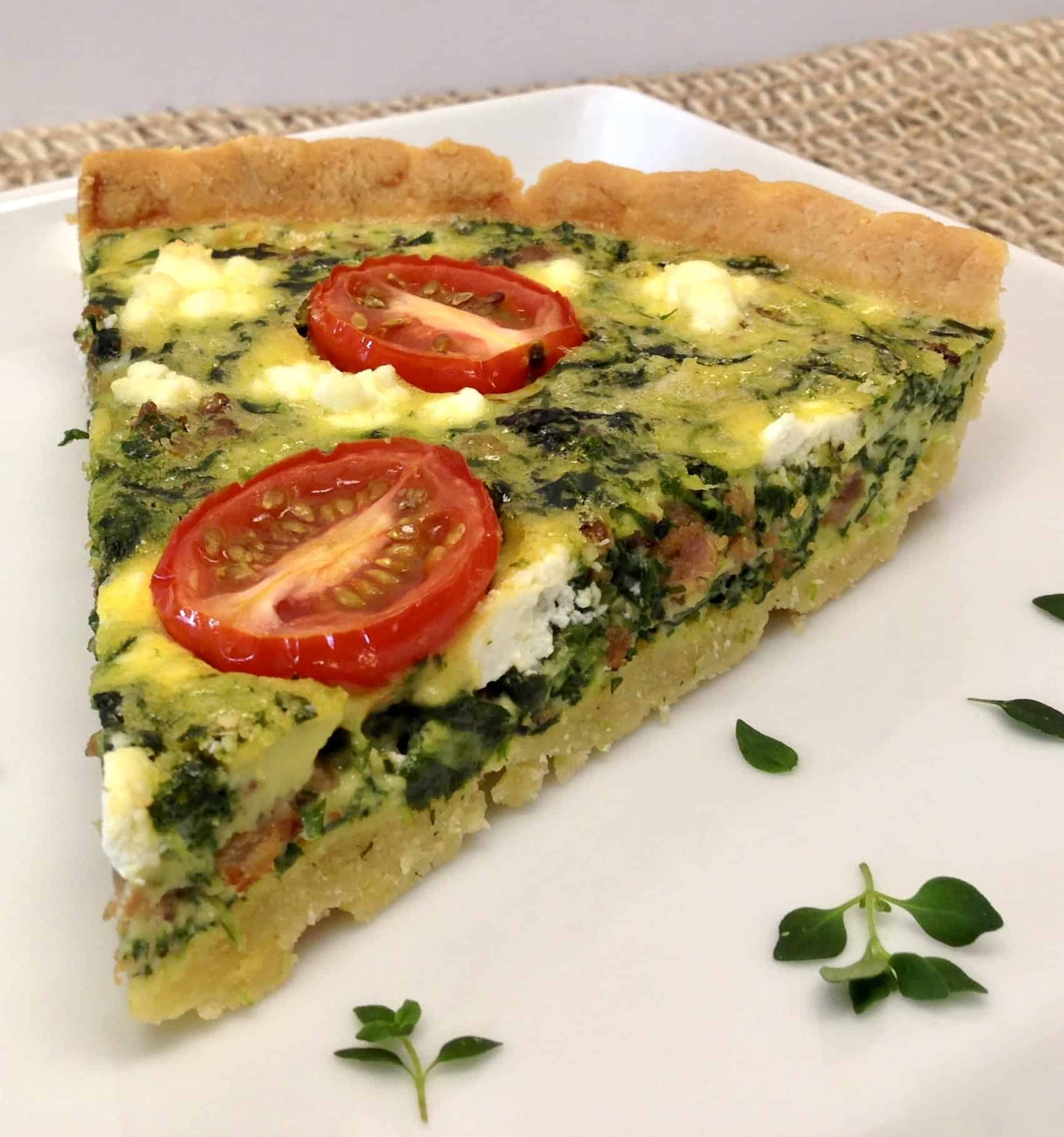 spinach quiche with tomatoes on plate