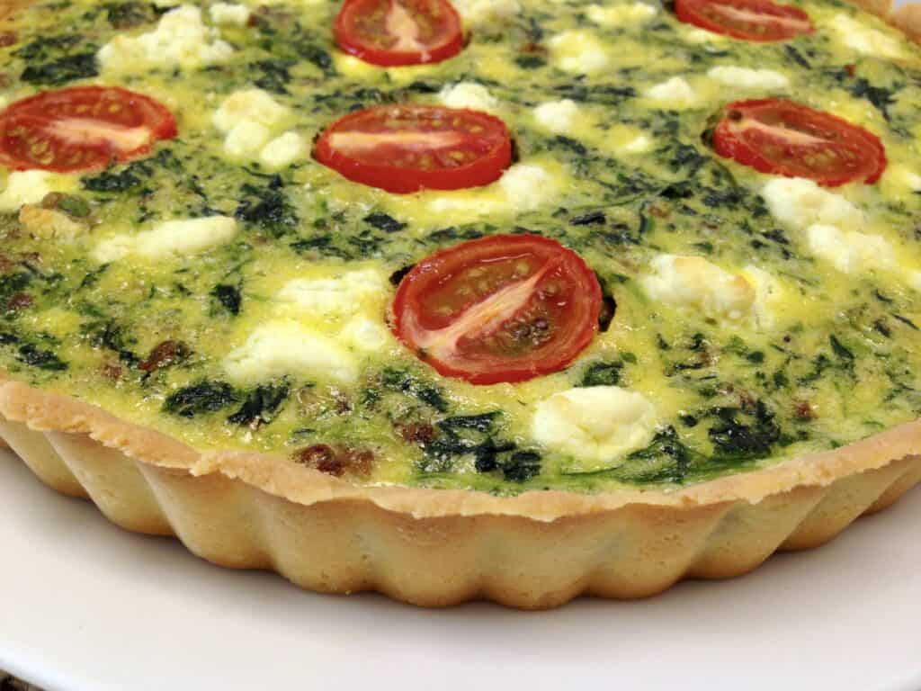 side view of spinach and tomato quiche