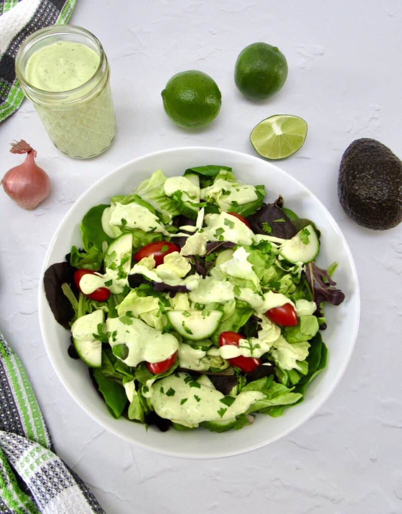 overhead view of salad with avocado ranch on top with dressing on the side