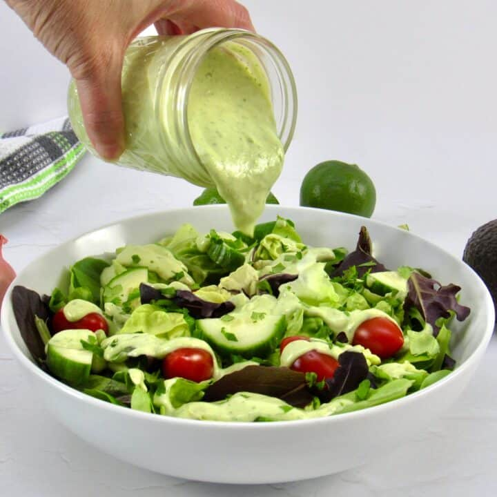 avocado ranch dressing being poured over salad