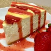 slice of cheesecake with strawberry sauce over the top