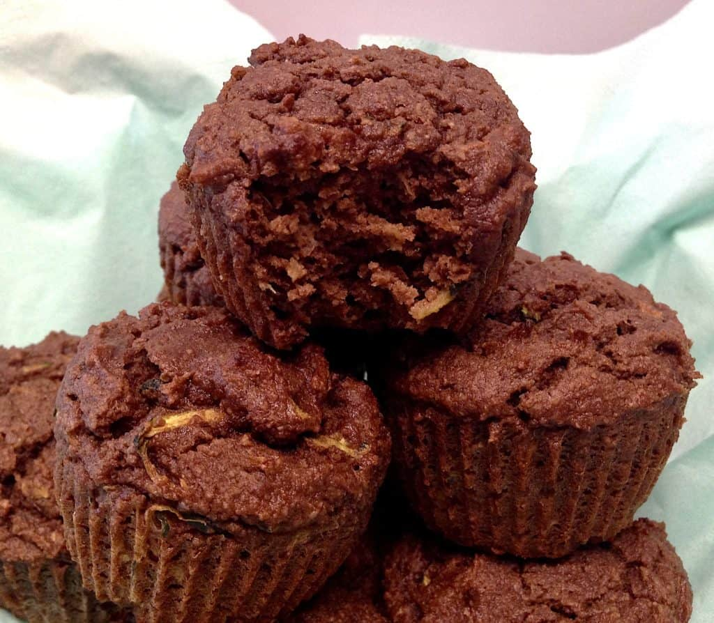 Keto Chocolate Zucchini Muffins stacked up with bite missing
