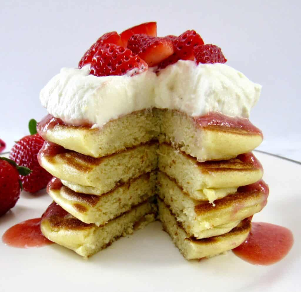 stack of pancakes with whip cream and strawberry sauce with piece missing