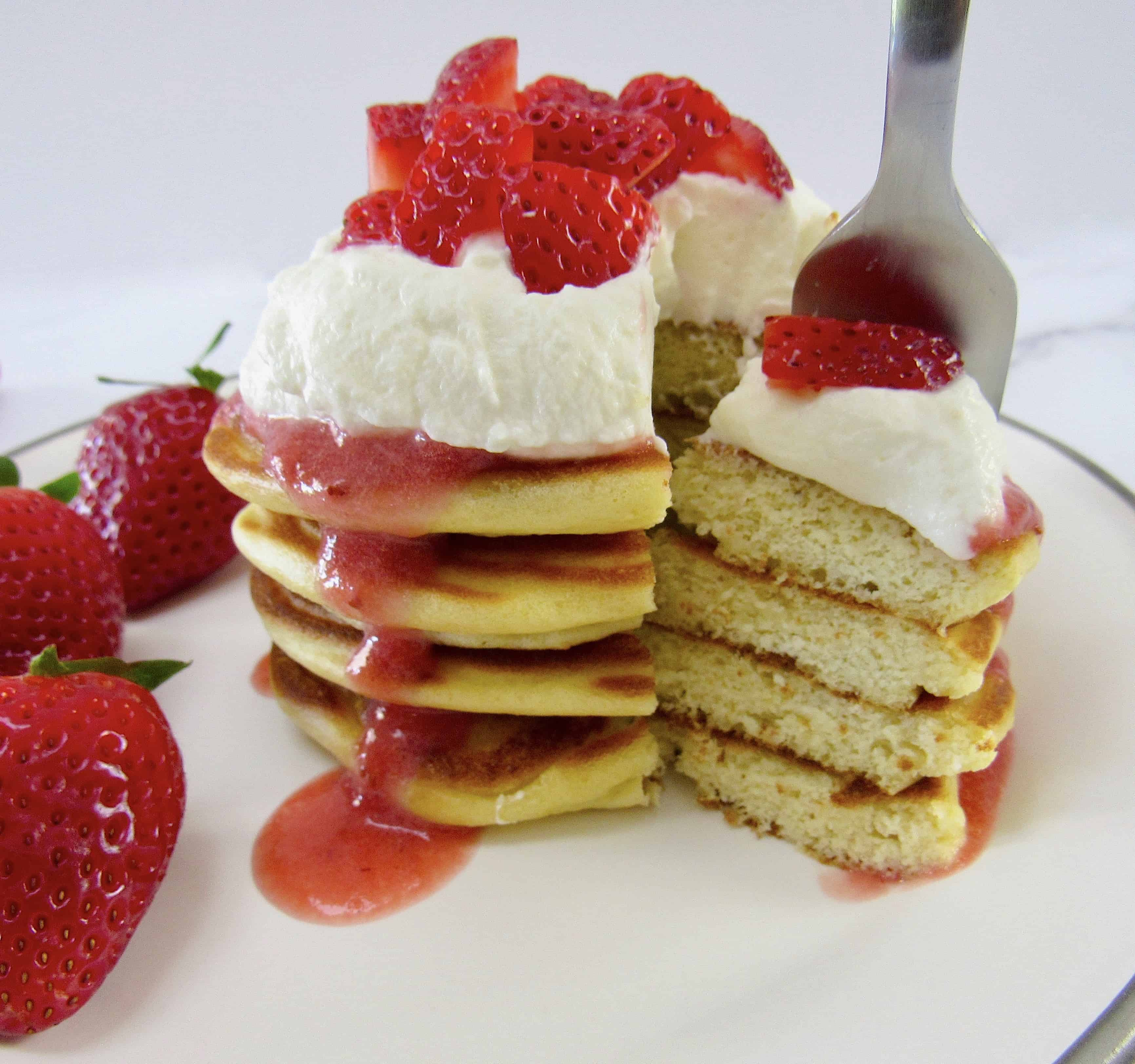 stack of pancakes cut with fork holding some