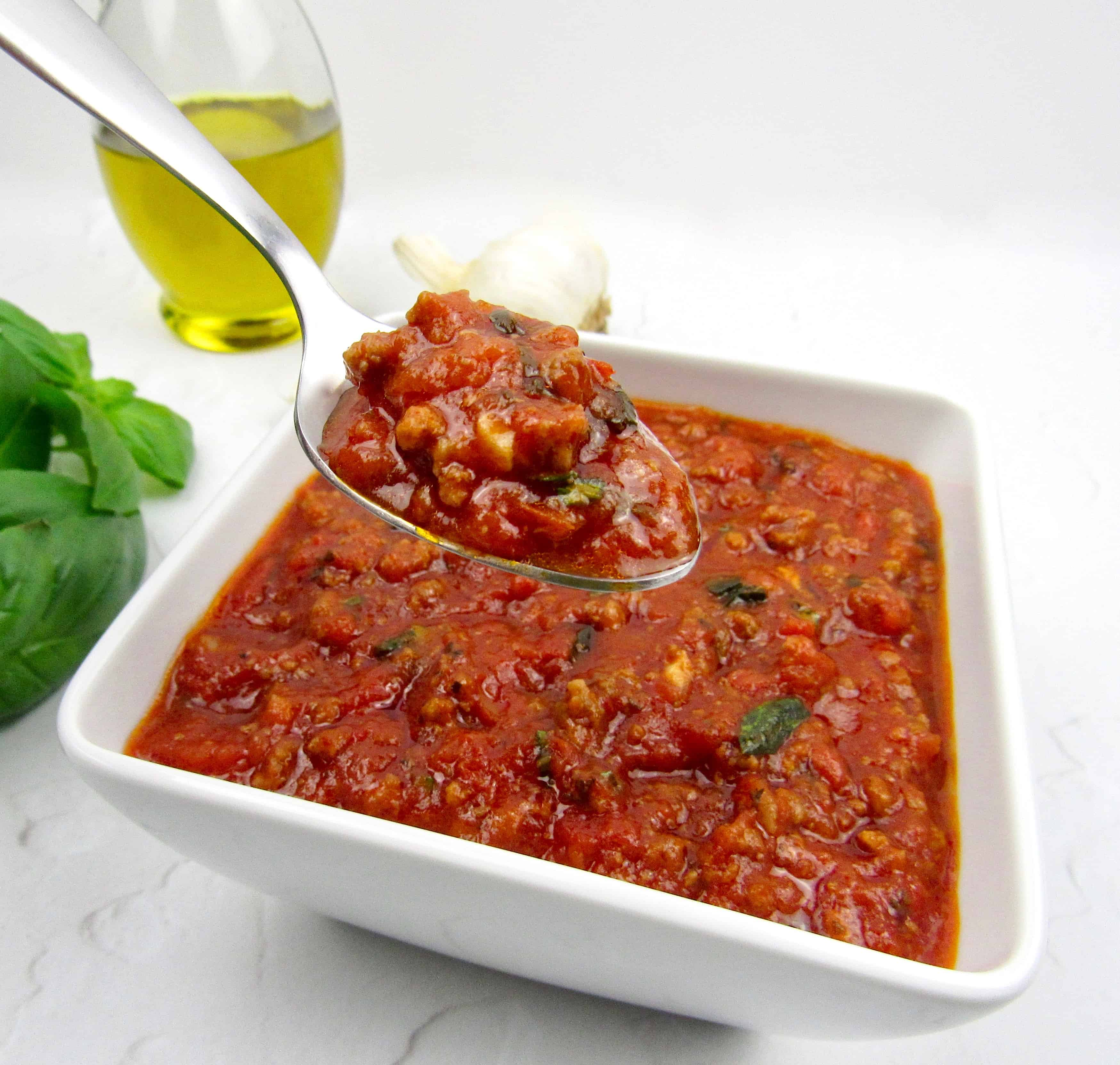 bowl with Italian meat sauce with spoon holding up some
