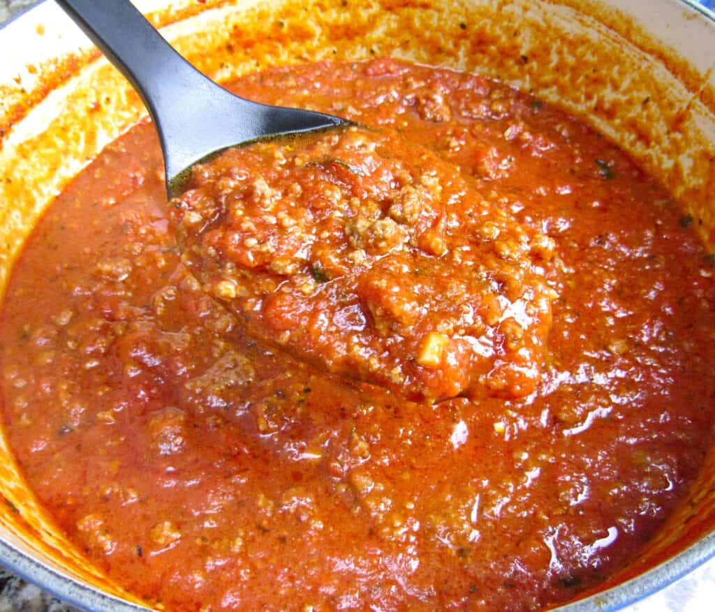 Italian meat sauce in pot with spoon holding some up