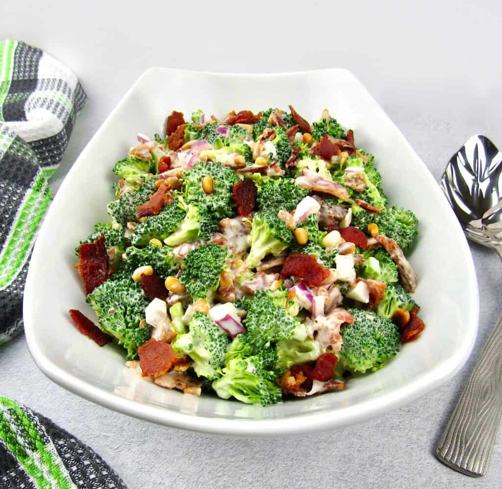 broccoli salad in white bowl topped with bacon