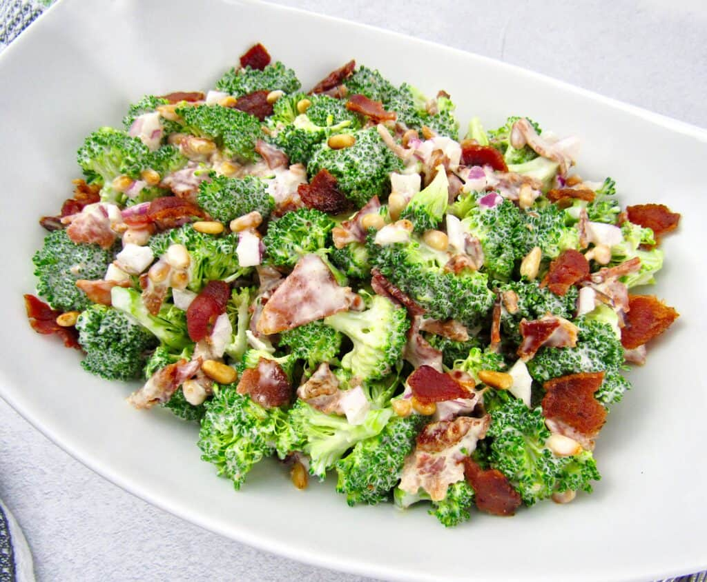 broccoli salad in white bowl topped with crumbled bacon