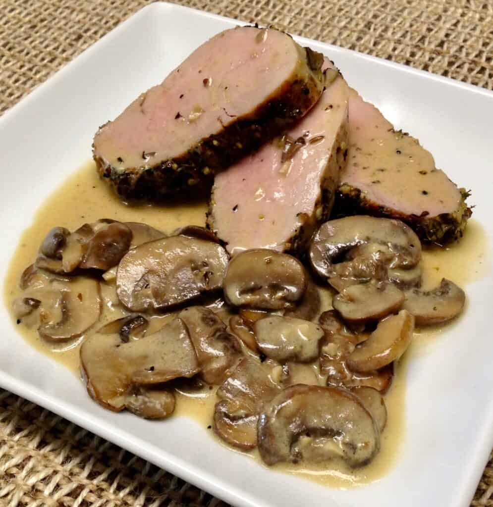 3 slices of pork tenderloin on white plate with mushrooms