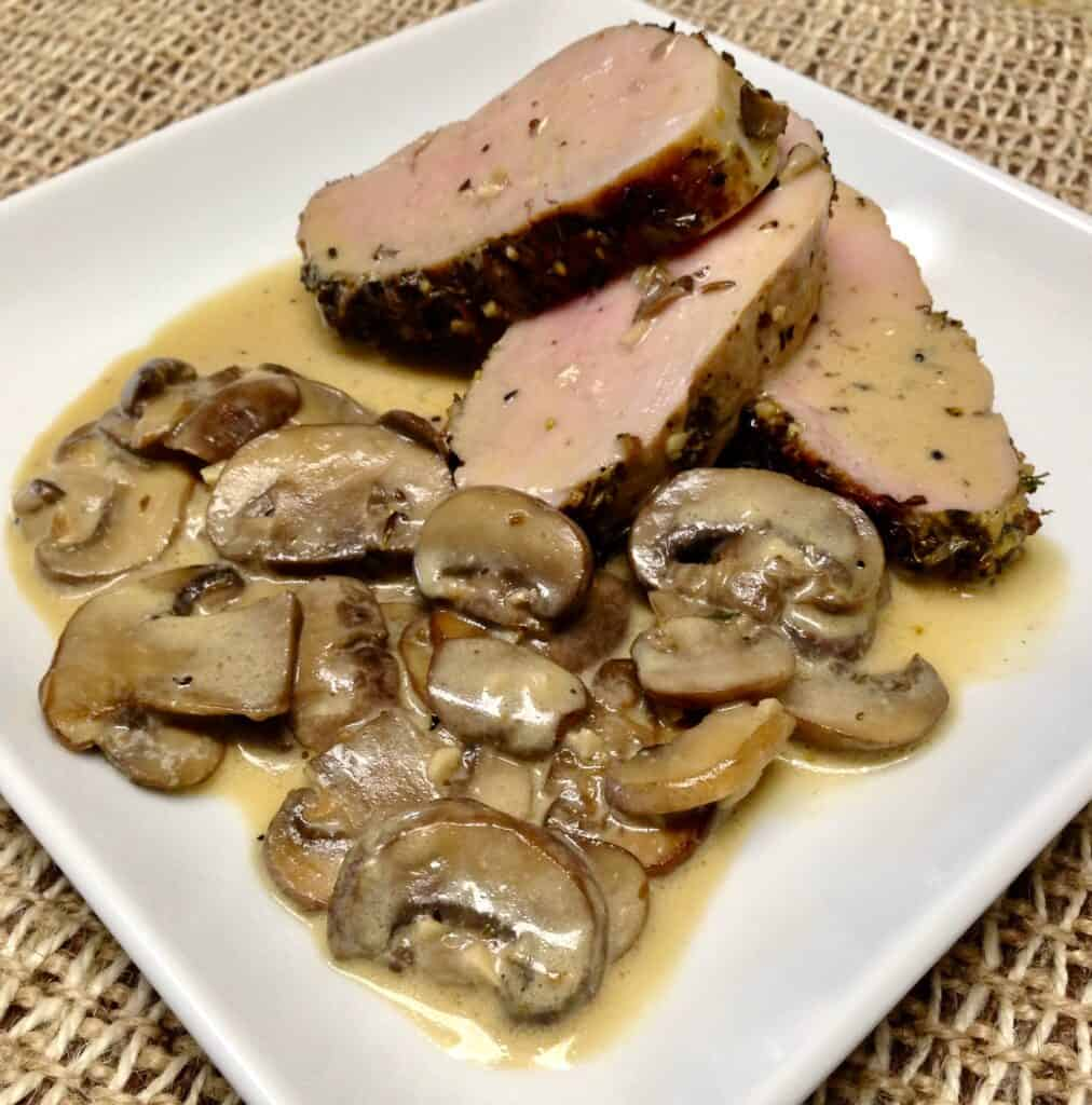 3 slices of pork tenderloin on plate with mushrooms