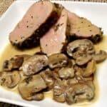 3 slices of pork tenderloin on white plate with mushrooms