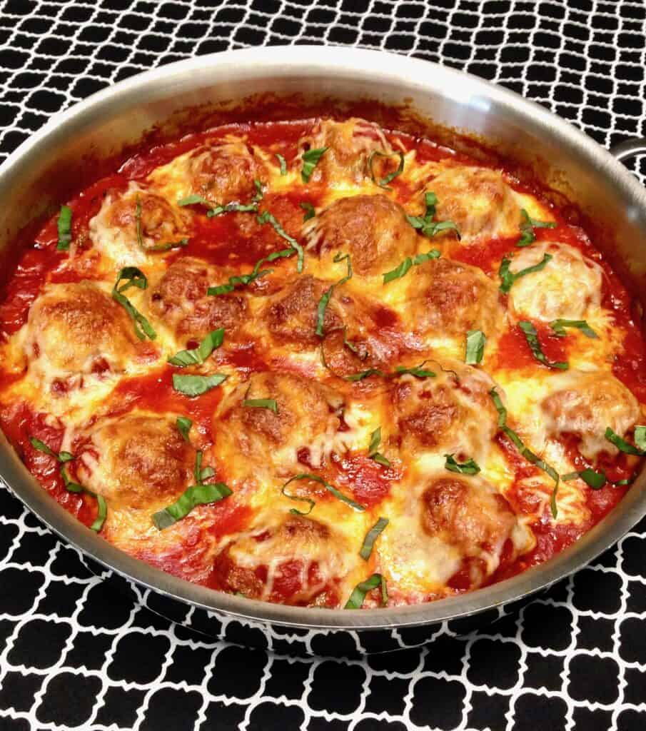 pan of baked meatballs with cheese and basil on top