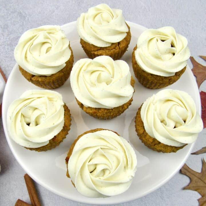closeup of 6 pumpkin cupcakes with vanilla frosting