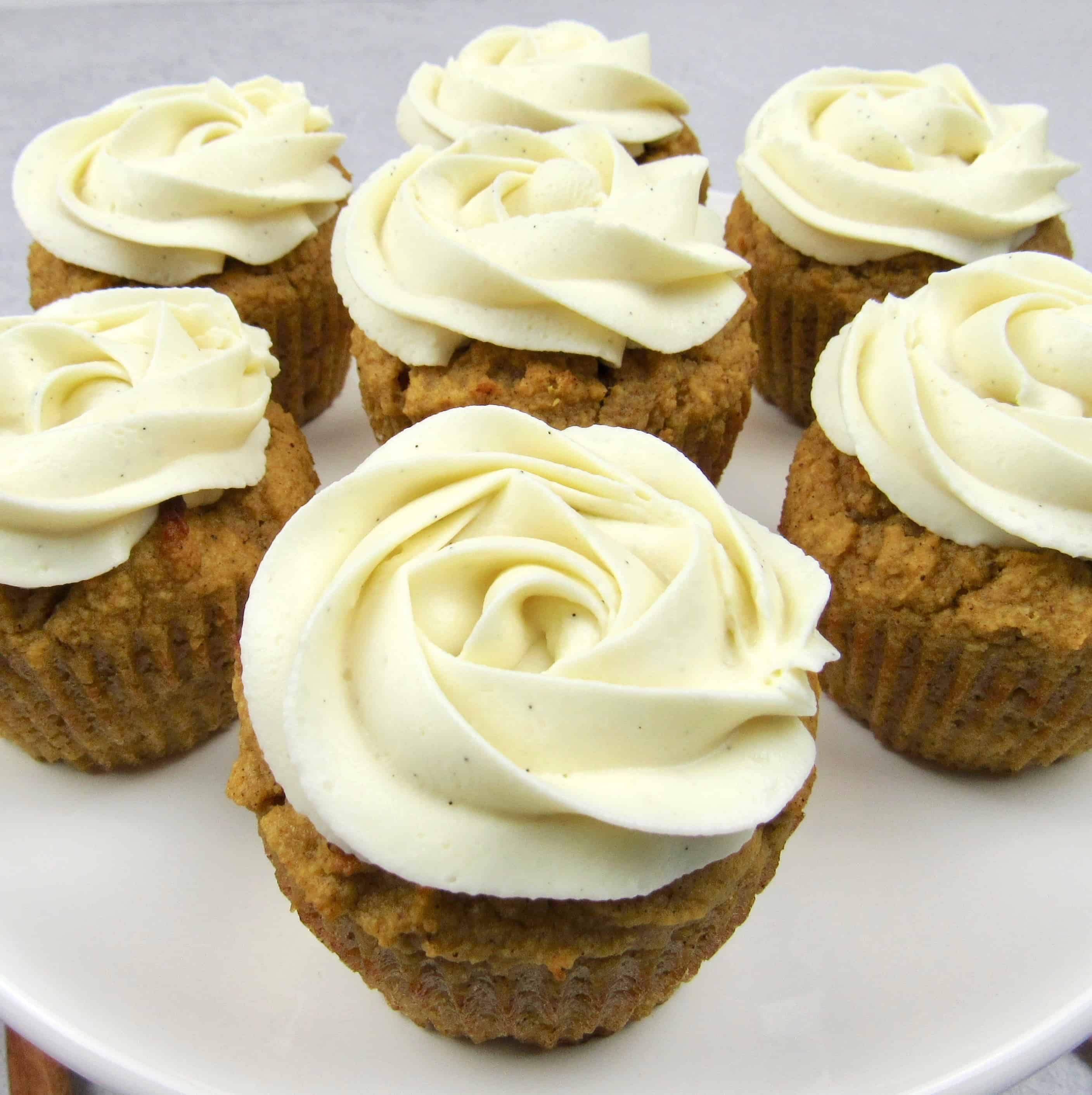 closeup of 6 pumpkin cupcakes with vanilla frosting