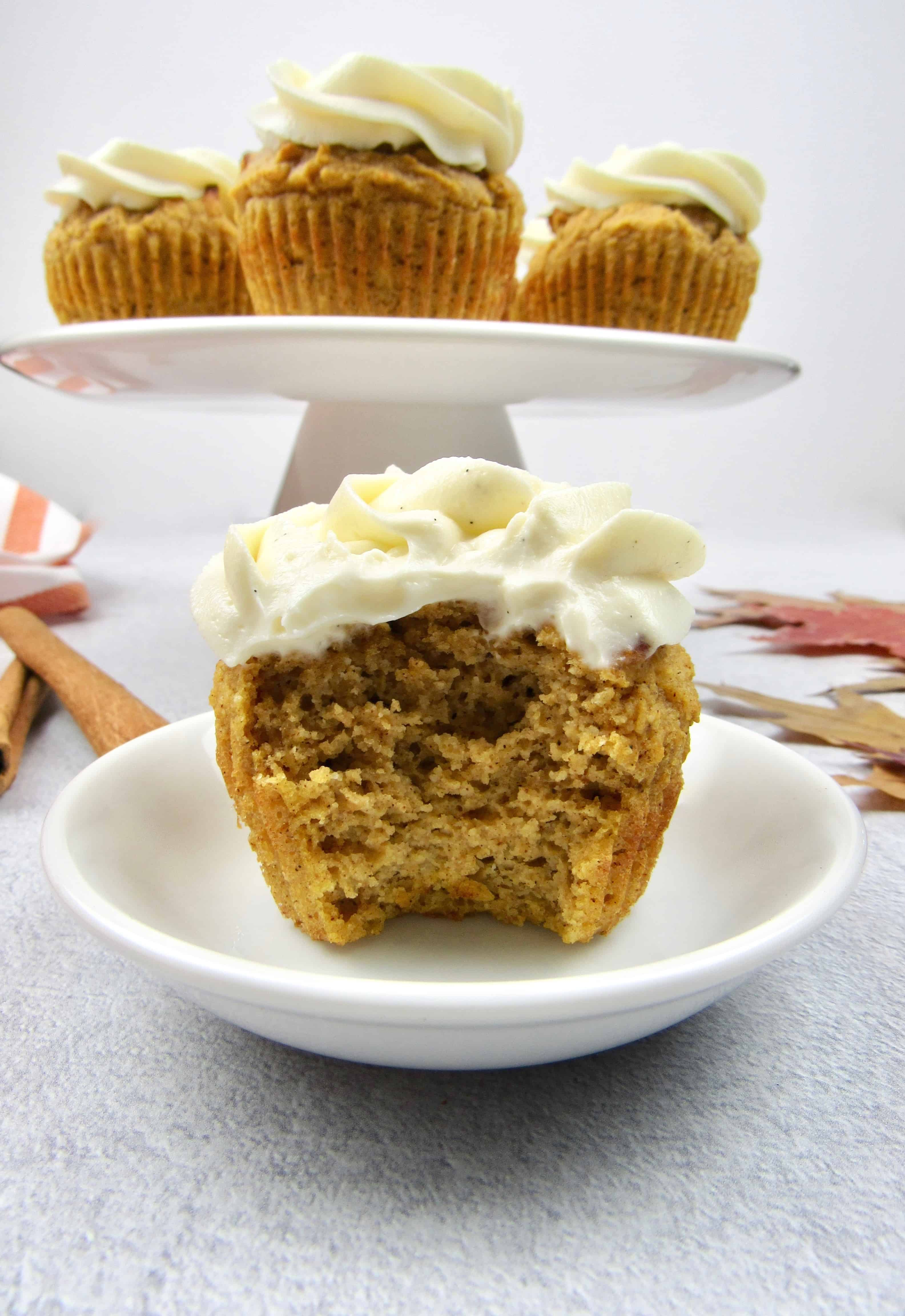 closeup of pumpkin cupcake with bite taken out with cupcakes in background