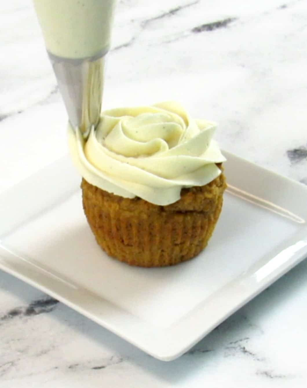 pumpkin cupcake being frosted
