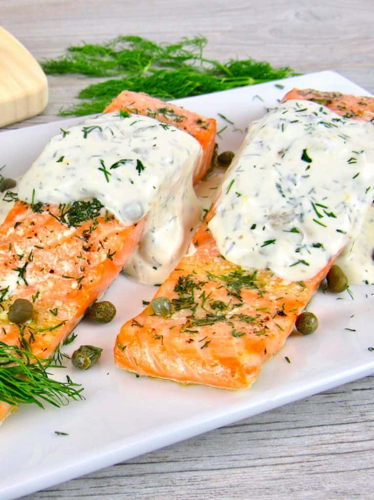2 pieces of salmon with dill sauce on top