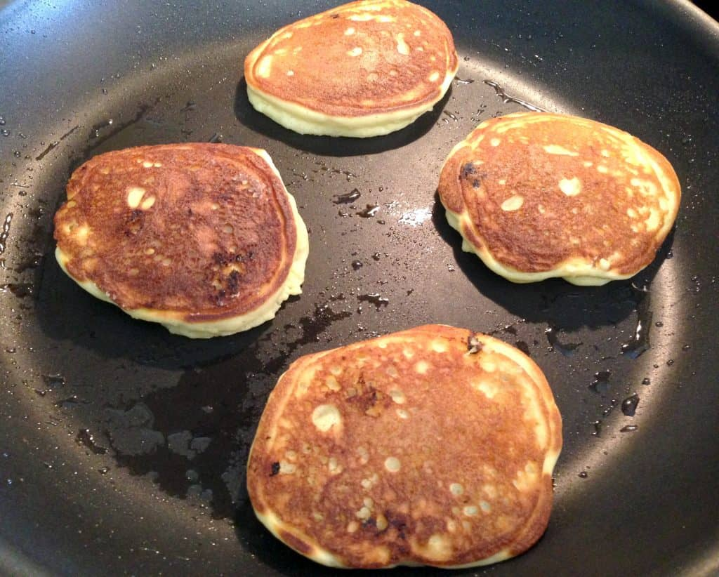 blueberry pancakes cooking in skillet